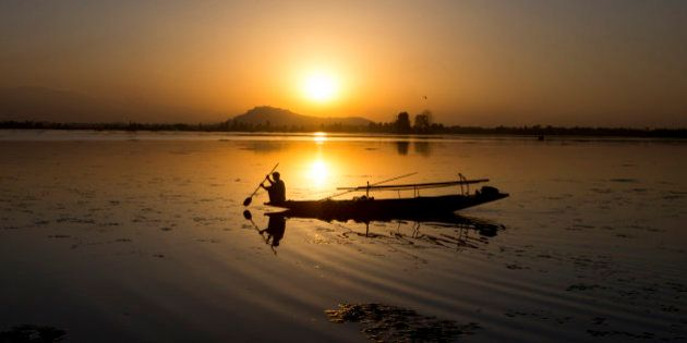 A Kashmiri fisherman rows his Shikara, or traditional boat, during sunset at the Dal Lake in Srinagar,...