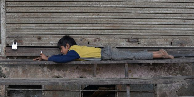 An Indian street child uses a cellphone outside a closed shop in New Delhi on December 7, 2015. AFP PHOTO/...