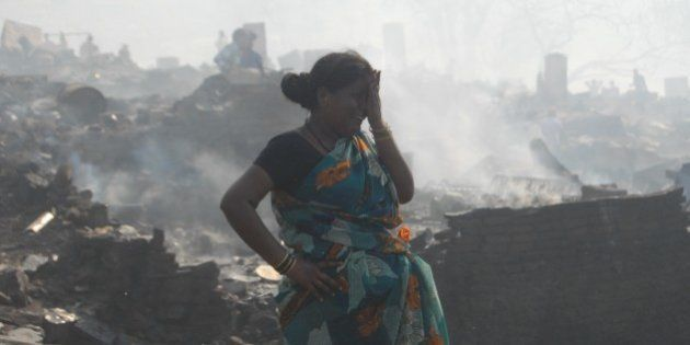 MUMBAI, INDIA - DECEMBER 7: An Indian woman cries as she tries to collect her belongings from the charred...