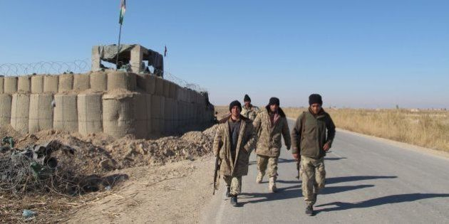 Afghan security forces patrol near their base in the Marjah district of Helmand Province on December...