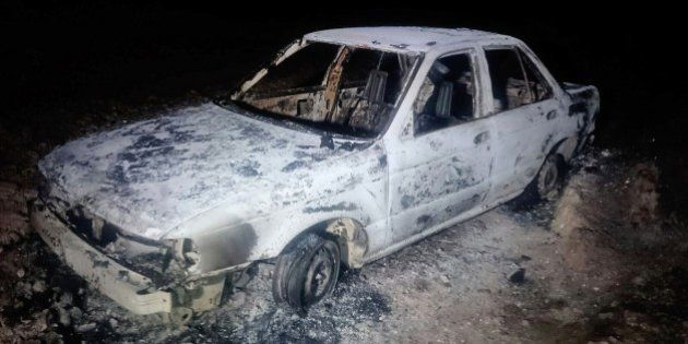 A burned down car remains at the crime scene where six people were executed by gunmen in Tetitlan de...