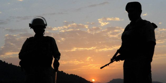 An Indian paramilitary soldiers stand guard as the sun sets over Dal Lake in Srinagar on June 20, 2011....