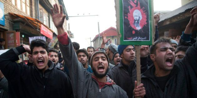 Kashmiri Shiite Muslims, carrying a placard with the portrait of Sheikh Nimr al-Nimr, shout slogans during...