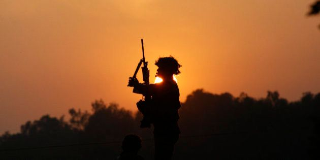 An Indian army soldier is silhouetted against the setting sun as he stands guard next to his colleague,...