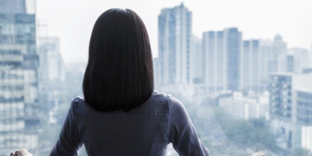 Rear view of a businesswoman looking out the window at the cityscape in Beijing,