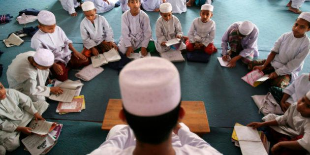 A madrasa, or Muslim religious school teacher teaches his students in Dhaka, Bangladesh, Sunday, April...