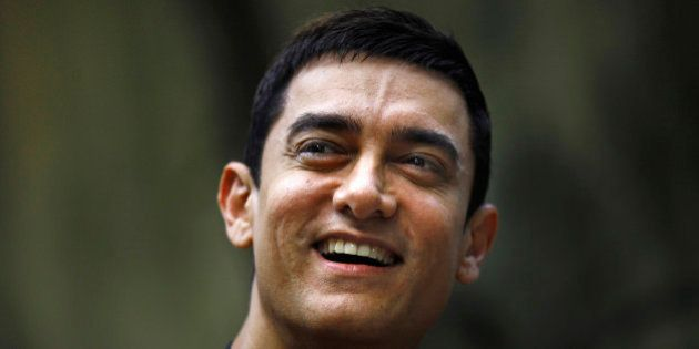 Bollywood actor Aamir Khan smiles as he takes questions from a journalist during a press conference to...