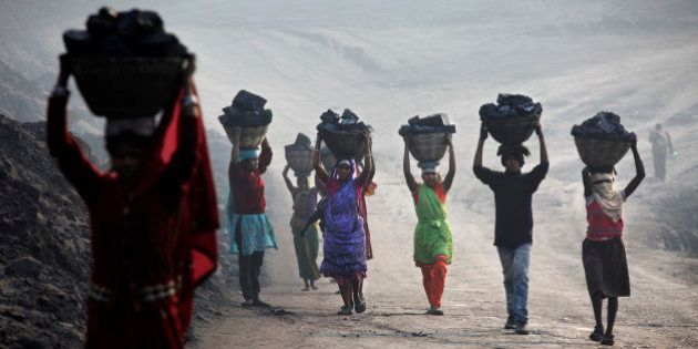 JHARKHAND, INDIA - DECEMBER 06: Villagers carry illegally scavenged coal from an open-cast coal mine...