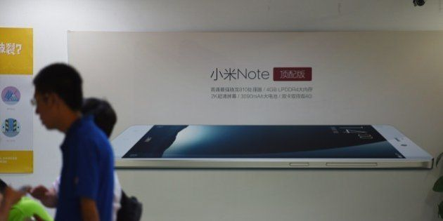 Customers wait near an advertisement for the Xiaomi Note mobile phone at a Xiaomi service center in Beijing...