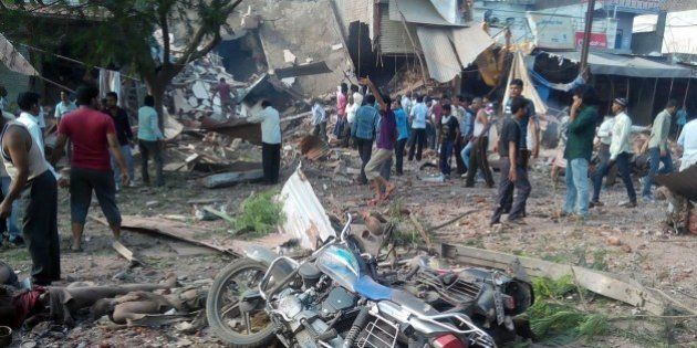 People gather around the site of an explosion at a restaurant in Jhabua district in the central Indian...