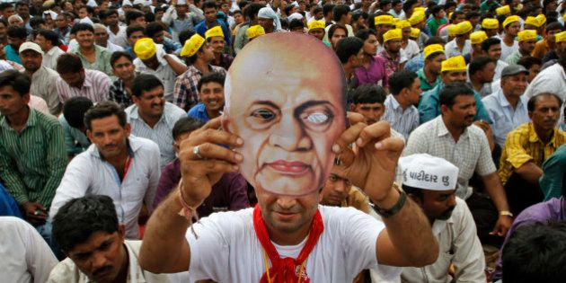 A Patidar or member of Patel community holds a mask of Indian freedom fighter and first Home Minister...