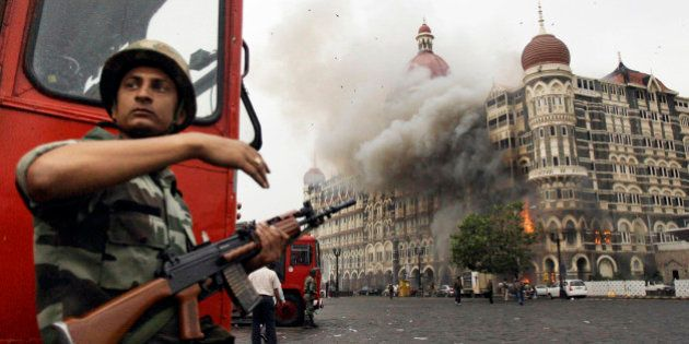 FILE- In this Nov. 29, 2008, file photo, an Indian soldier takes cover as the Taj Mahal hotel burns during...