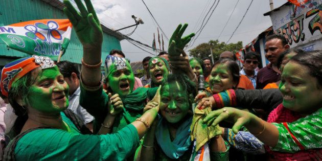 Supporters of Trinamool Congress (TMC) celebrate after learning the initial poll results of the West...