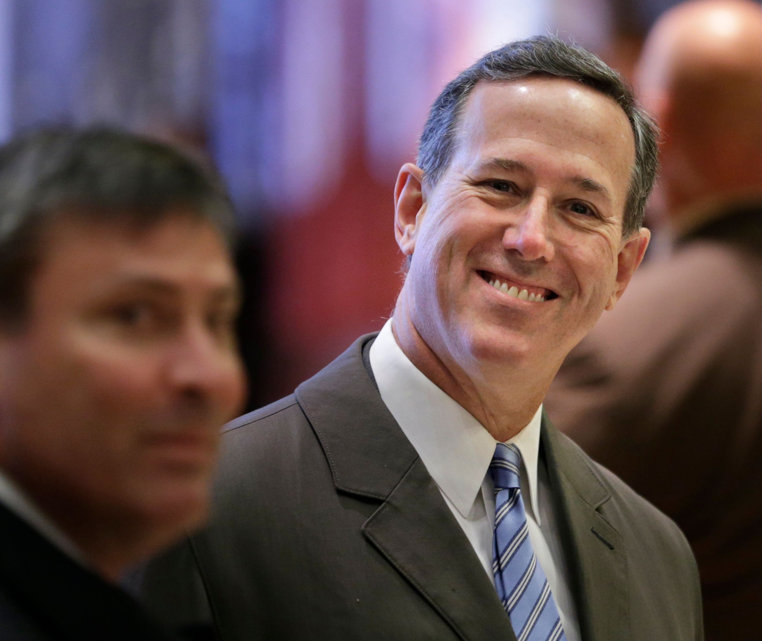 Former Pennsylvania Sen. Rick Santorum smiles at reporters while waiting for an elevator in Trump Tower in New York, Tuesday, Dec. 13, 2016. (AP Photo/Seth Wenig)