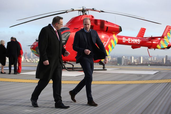 The Duke of Cambridge walks across the helipad after arriving in a red London Air Ambulance at the Royal London Hospital in e