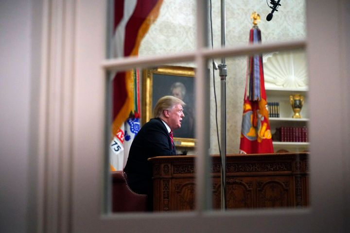 As seen from a window outside the Oval Office, President Donald Trump gives a prime-time address about border security Tuesda