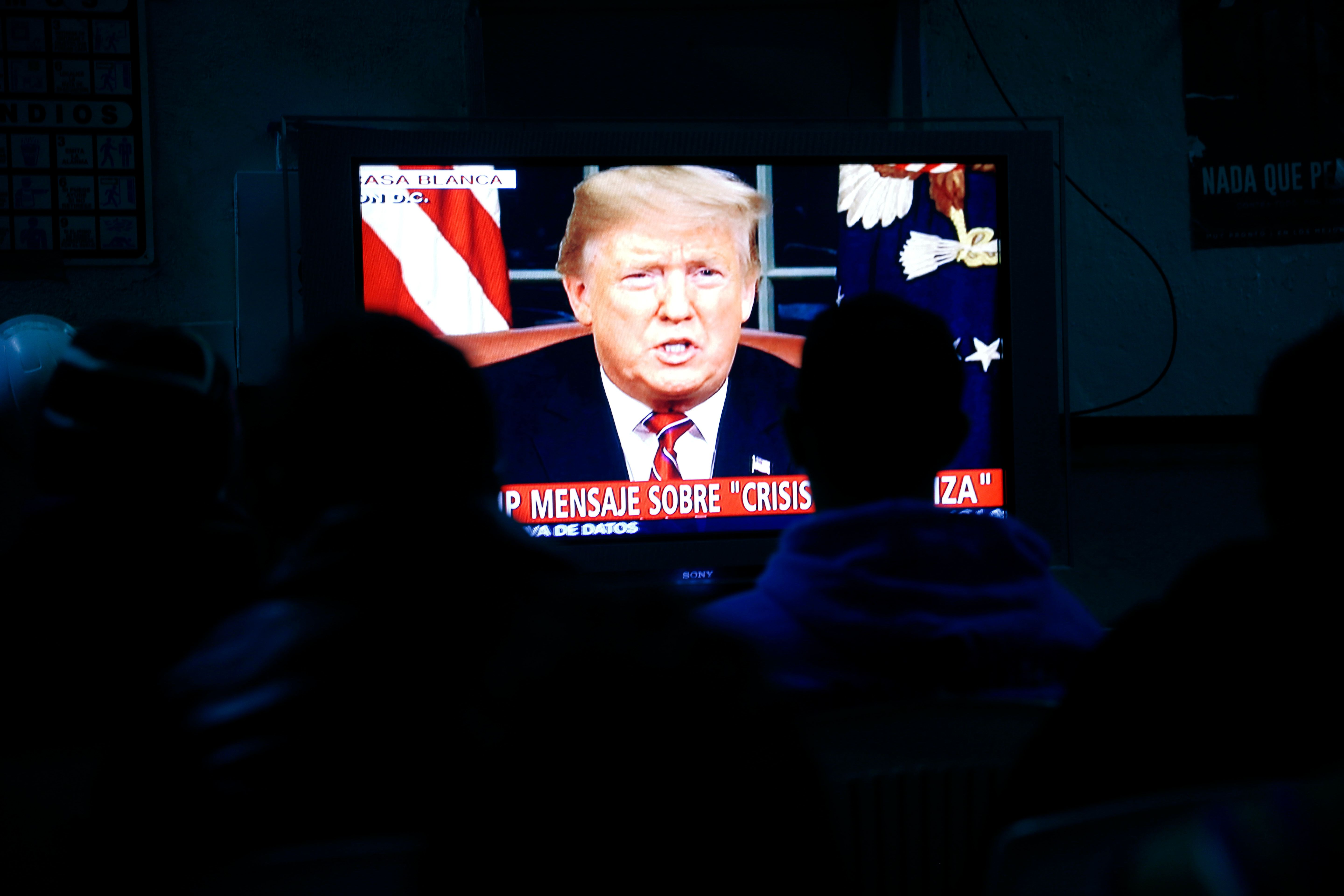 Migrants mainly from Mexico and Central America look on as U.S. President Donald Trump gives a prime-time address about border security Tuesday, Jan. 8, 2019, watching from a border migrant shelter in Tijuana, Mexico. (AP Photo/Gregory Bull)