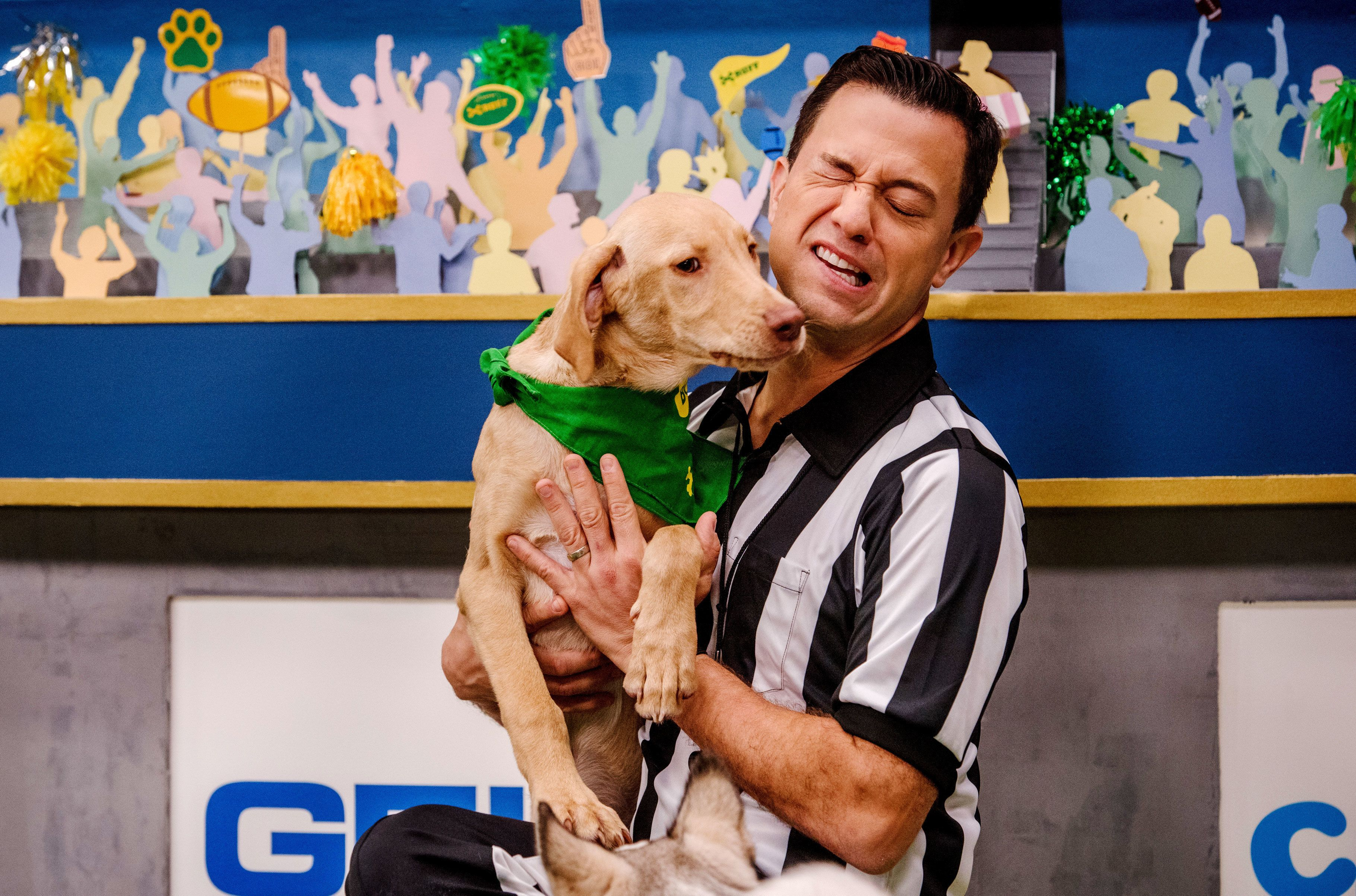 Dan Schachner, aka Dan the Ruff-eree, holds up touchdown-scorer Hank during the filming of the Puppy Bowl in New York City on