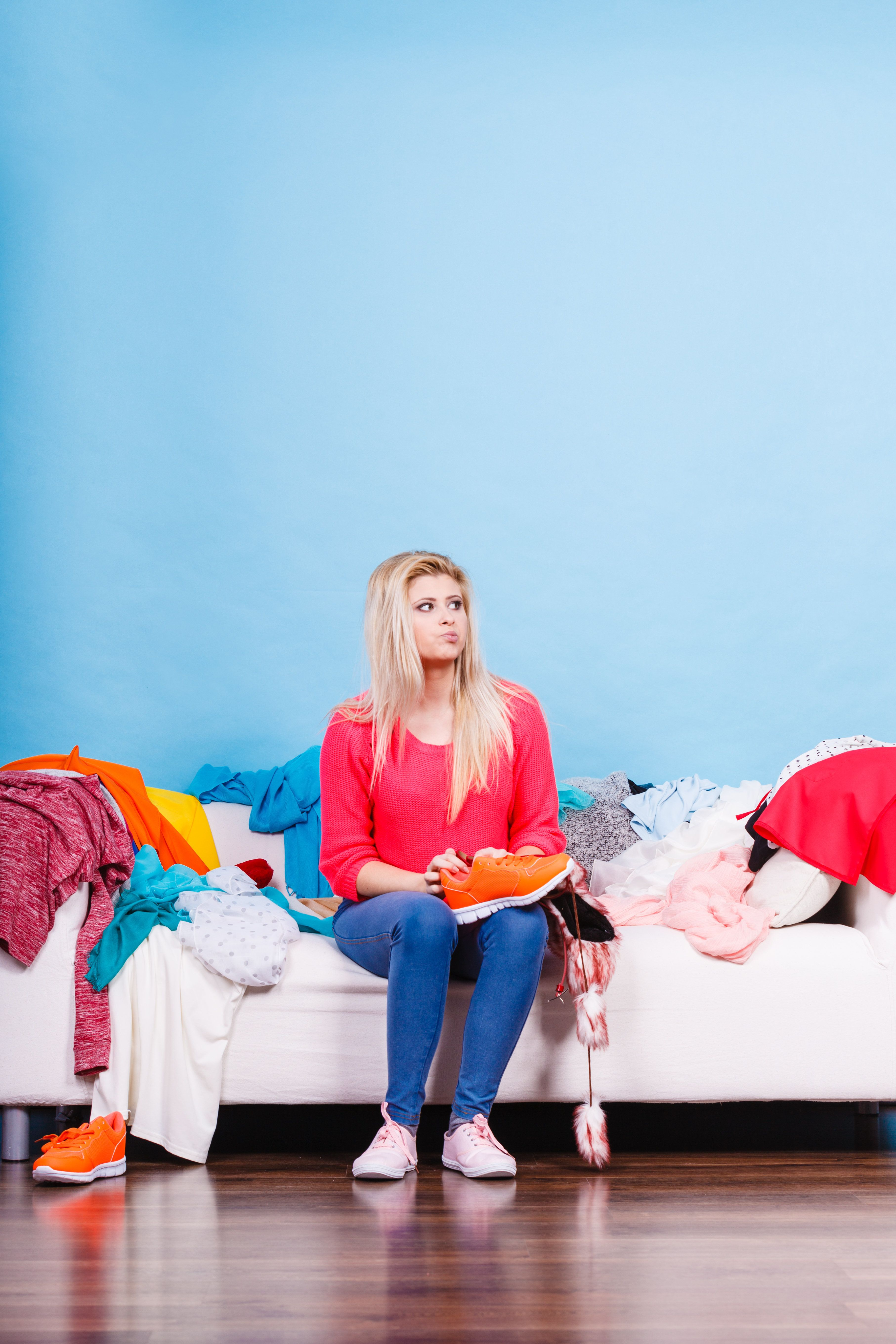 Clothing dilemmas concept. Woman does not know what to wear sitting on messy couch with piles of clothes.