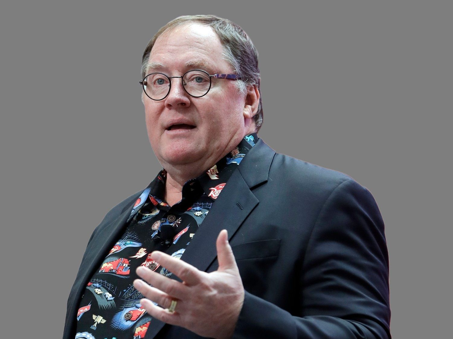 John Lasseter headshot, Pixar co-founder and Walt Disney Animation Studio chief, graphic element on gray