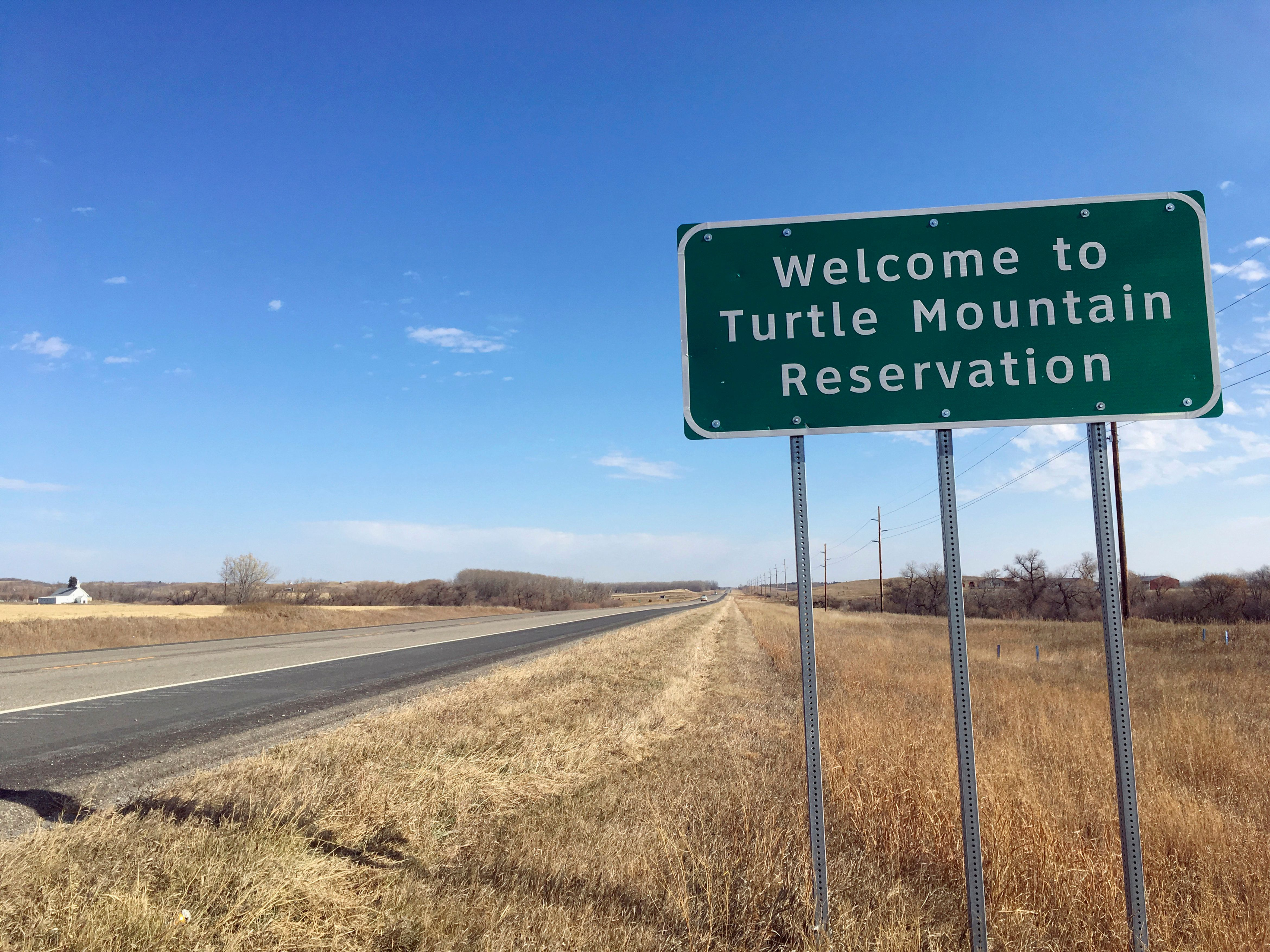 File - In this Wednesday, Oct. 24, 2018, file photo, a sign to the Turtle Mountain Reservation of Native Americans in North Dakota is shown before Election Day amid concerns over voter ID. A new report released Thursday, Dec. 20, 2018, by the U.S. Commission on Civil Rights finds that funding levels for Native American tribes are woefully inadequate despite the federal government's responsibility to provide for education, public safety, health care and other services under treaties, laws and other acts. (AP Photo/Blake Nicholson, File)