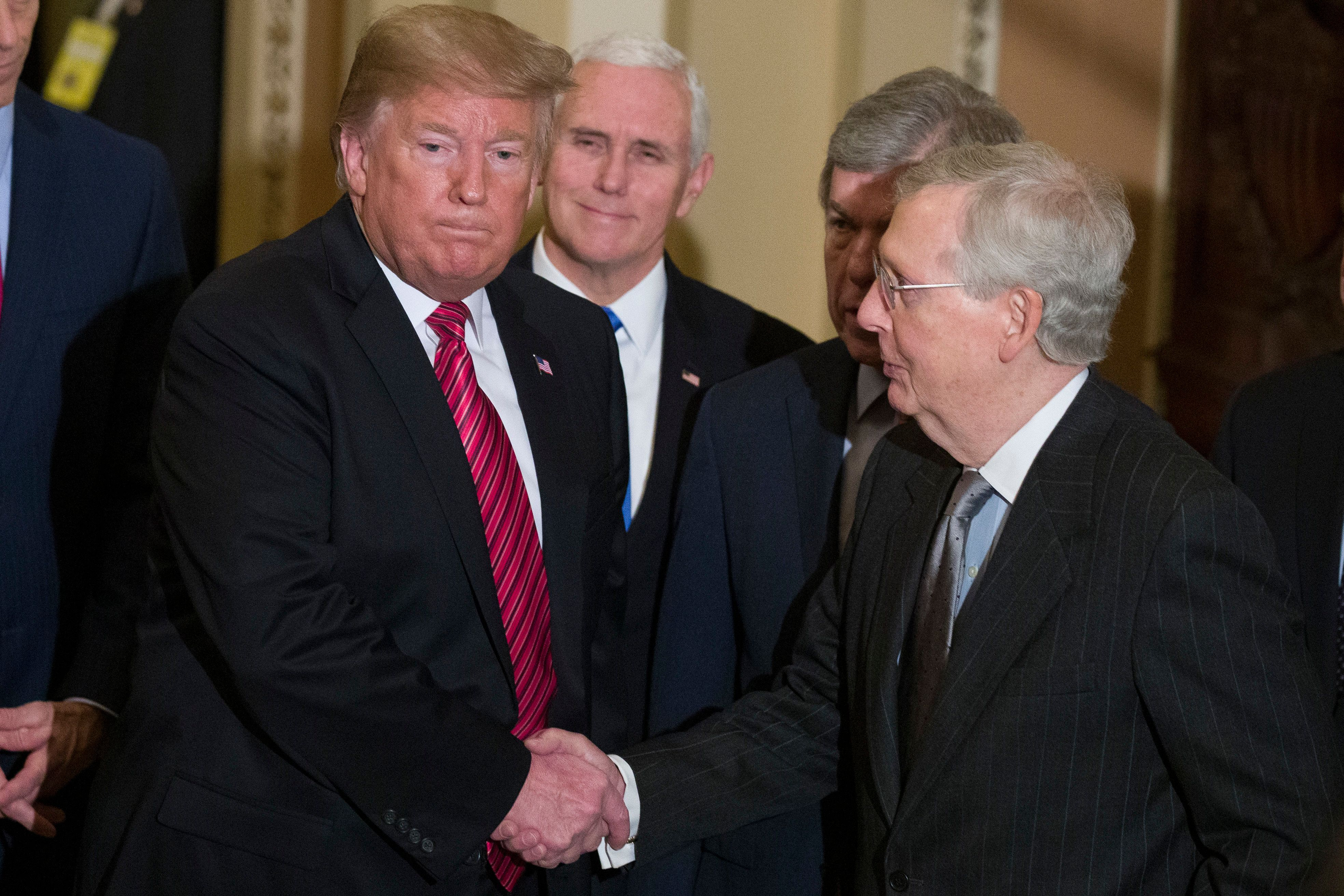 President Donald Trump shakes hands with Senate Majority Leader Mitch McConnell of Ky., as he departs accompanied by Vice President Mike Pence after a Senate Republican Policy luncheon, on Capitol Hill in Washington, Wednesday, Jan. 9, 2019. (AP Photo/Alex Brandon)