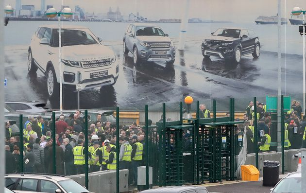 Staff gather outside the Jaguar Land Rover site in Halewood, Knowsley, Merseyside. The luxury carmaker...