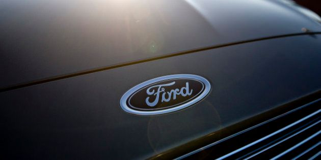 A Ford Motor Co. emblem appears above the grille of a 2014 Ford Fusion at Uftring Ford in East Peoria,...