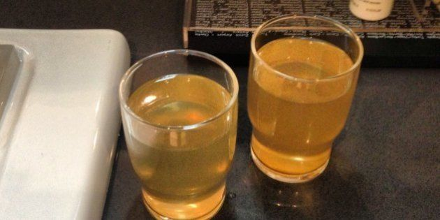 Drinking glasses show yellow-colored water poured from a bathroom faucet at a Sochi, Russia, hotel on...