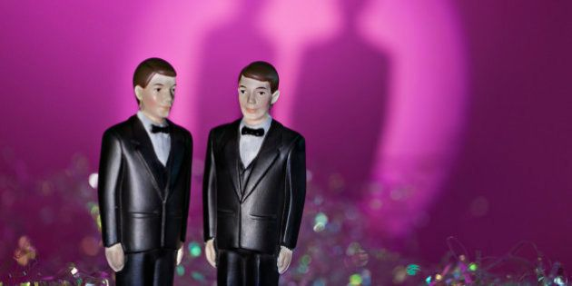 Two male figurines in formal attire illustrate same sex union. Pink and rainbow background with shadows...