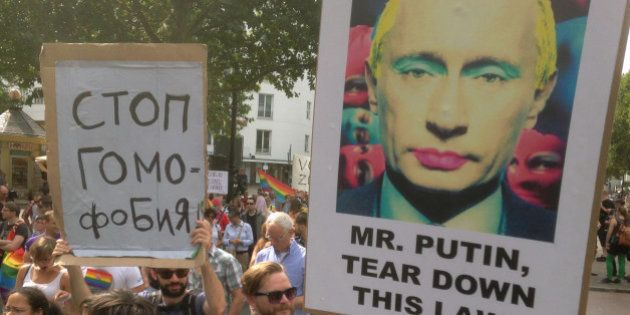 A demonstrator holds a poster with the portrait of Russian President Vladimir Putin during a protest...