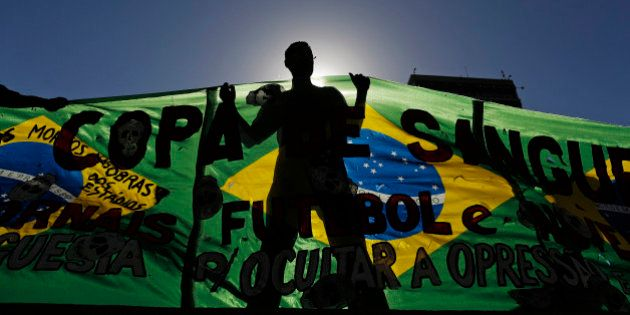 An Anti-World Cup demonstrator holds a banner during a protest near Maracana stadium on the last day...