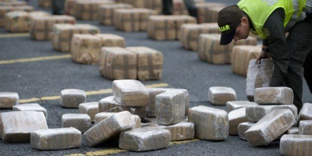 A Colombian anti-drugs police officer checks packages of marijuana, part of a load of five tons seized...