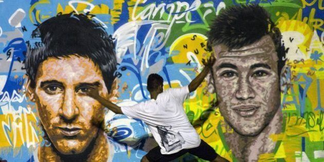Youngsters play football in front of a mural of Argentine football player Lionel Messi (L) and Brazil's...