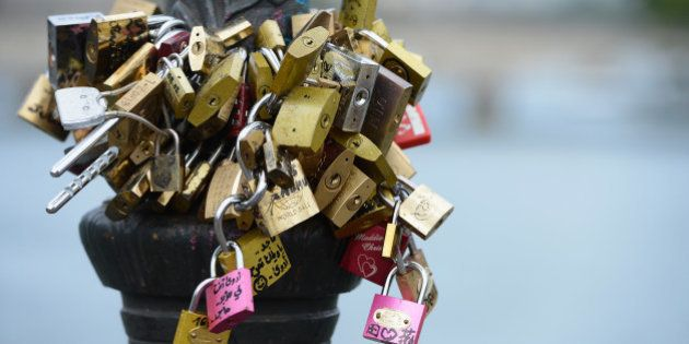 PARIS, FRANCE - AUGUST 19: Love padlocks are attached to Le Pont Des Arts on August 19, 2013 in Paris,...