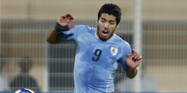 Oman's Ali al-Busaidi (bottom) defends against Uruguay's Luis Suarez (#9) during their friendly football...