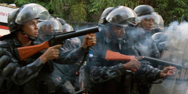 Riot policemen confront demonstrators during a protest against a hike on bus fare in Rio de Janeiro,...
