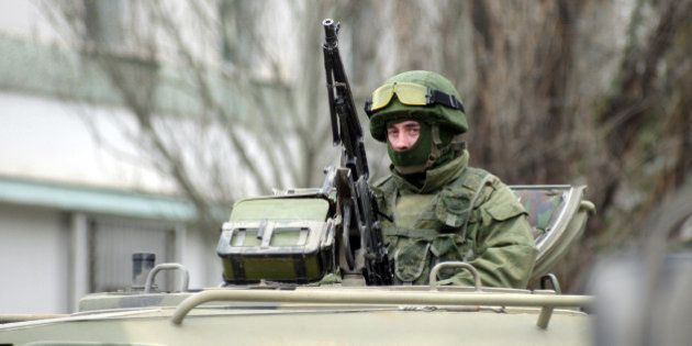 An unidentified armed individual in an armoured vehicle blocks the base of the Ukrainian border guard...