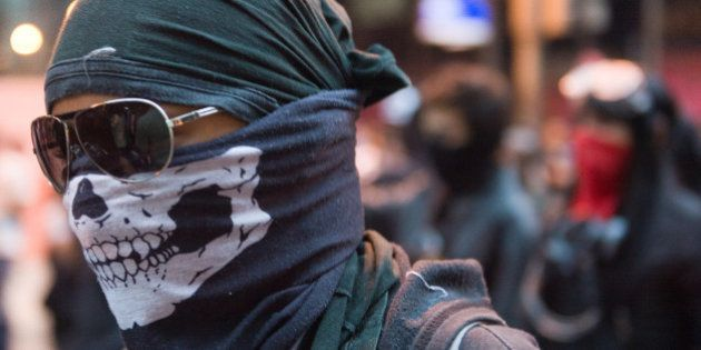 A demonstrator member of the 'Black Bloc' takes part in a protest to demand better working conditions...