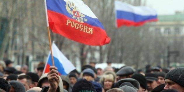 A pro-Russian activist holds a Russian flag during a rally in the center of the eastern Ukrainian city...