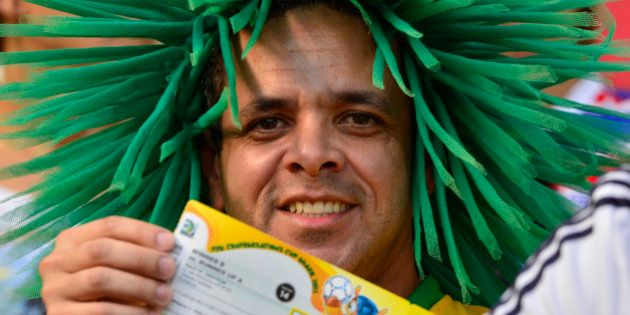A football fan with the colours of Brazil shows a match ticket as he waits for the start of the FIFA...