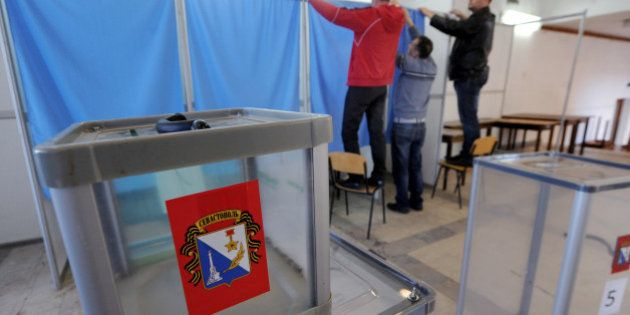 Employees prepare the polling booth in one of the polling stations of Sevastopol on March 15, 2014, on...