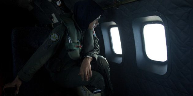 A crew member looks out the windows from a Malaysian Air Force CN235 aircraft during a search and rescue...