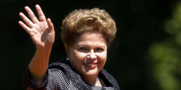 Brazilian President Dilma Rousseff waves at the press in Vina Del Mar, Chile on March 11, 2014 after...