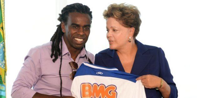 Brazilian President Dilma Rousseff (R) receives a Cruzeiro jersey from footballer Tinga during a meeting...