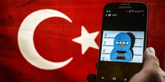A picture representing a mugshot of the twitter bird is seen on a smart phone with a Turkish flag on...