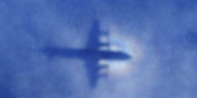 This shadow of a Royal New Zealand Air Force P3 Orion aircraft is seen on low cloud cover while it searches...