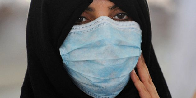 A Muslim pilgrim wearing a mask due to fears of the deadly MERS virus arrives to throw pebbles at pillars...