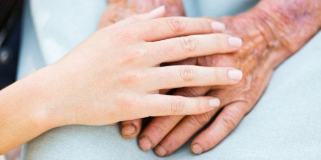 caring woman hands over elderly