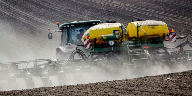 A farmer drives a Deere & Co. tractor across a field while planting corn seeds in the countryside outside...